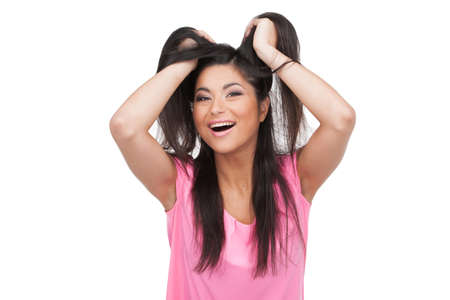 Happy woman holding her hair looking at camera. Standing in pink over white background photo