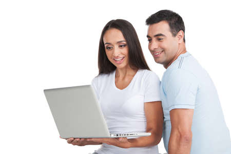 Indian loving  couple looking at laptop. Sitting and smiling isolated on white background photo