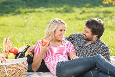What a beautiful day! Loving young couple enjoying an intimate picnic together photo