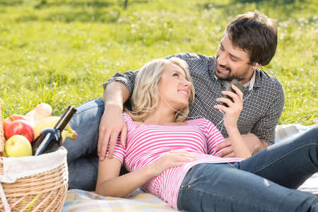 Listening to the music together. Loving young couple listening to the music on picnic together photo