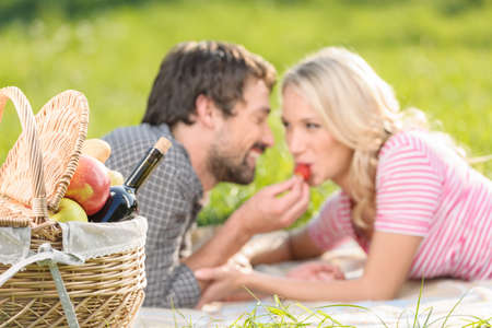 A strawberry for her. Young men feeding his girlfriend with strawberry lying on the grass in spring park photo