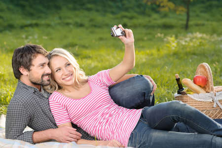 It will be the great shot. Loving young couple taking the photographs of themselves on summer picnic photo