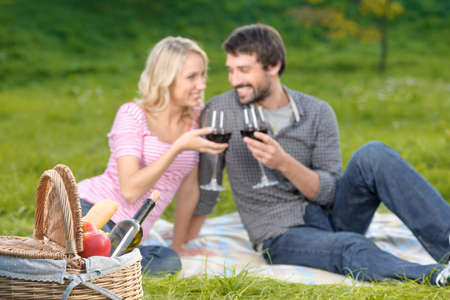 Cheers! Loving young couple enjoying wine on a picnic together photo