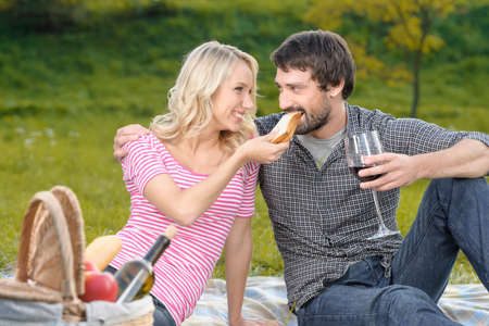 Who is the most hungry? Beautiful young woman feeding her boyfriend with a sandwich on the picnic photo