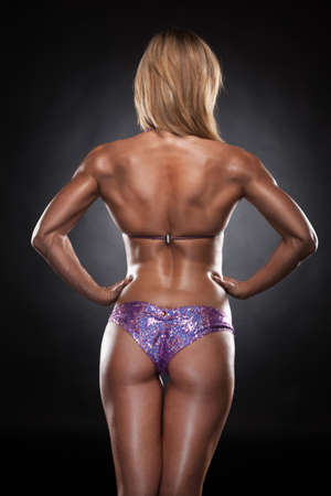 Back of Sexy fit woman in swimming suit. Back view of bodybuilder isolated on black photo