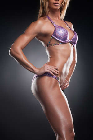 Cut out of female bodybuilder body. Standing in swimsuit isolated over black background photo