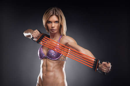 Beautiful fit blond girl doing exercise on her hands. Bodybuilder Training over black background photo