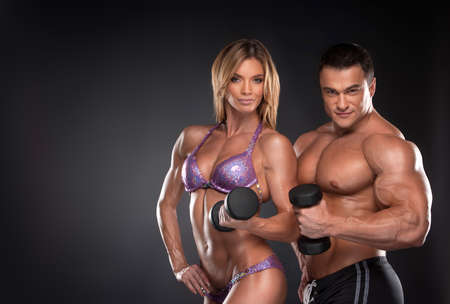 human muscle: Couple of well trained bodybuilder with dumbbells. Woman and man standing over black background