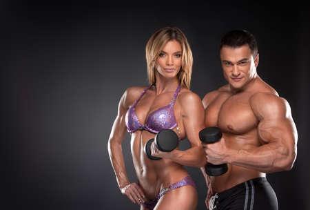 atletisch: Paar van goed opgeleide bodybuilder met halters. Vrouw en man staande op zwarte achtergrond Stockfoto
