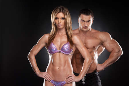 Sexy couple of fit man and woman showing muscular.  Bodybuilder standing together isolated over black background photo