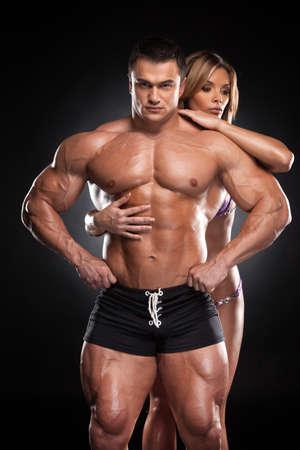 Sexy fit blonde Mädchen umarmt von hinten männliche Bodybuilder. Stehen zusammen auf schwarzem Hintergrund