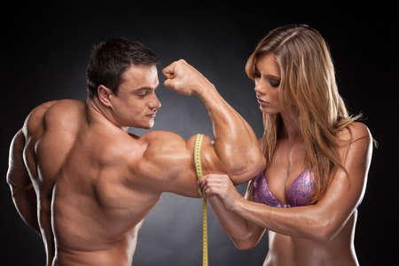 Sexy blonde Frau fit Maßnahme Hand männlich muskulös. Stehen zusammen auf schwarzem Hintergrund isoliert