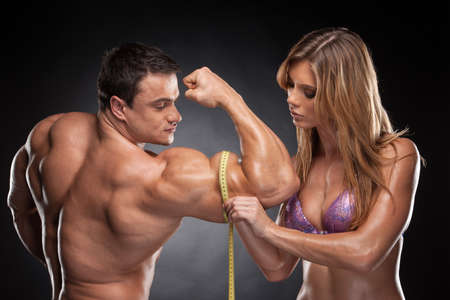 measuring: Sexy fit blond woman measure hand male  muscular. Standing together isolated over black background
