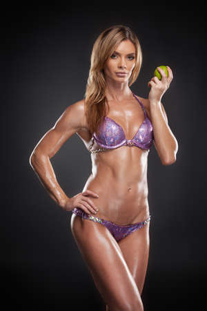 part body: Beautiful blond girl with perfect figure holding apple. Idea of healthy nutrition and diet. Stock Photo