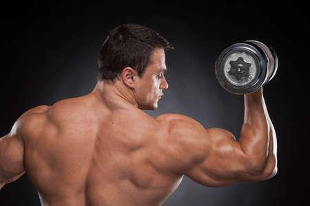 ビュー筋肉男持ち上がるダンベルをバックアップします。黒の背景上分離トレーニング