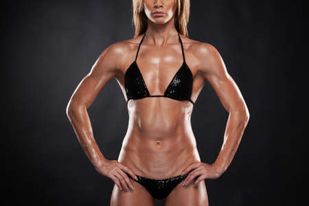 Beautiful sexy blond bodybuilder woman  lifting hands up. Standing isolated on black background photo