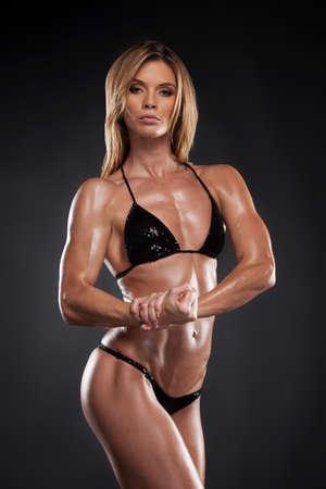 culturista: Mujer sexy fisicoculturista rubia en bikini negro. Posando y mostrando muscular en fondo negro