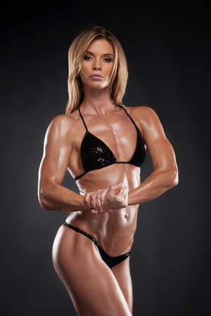 Sexy blond bodybuilder woman in black bikini. Posing and showing muscle on black background