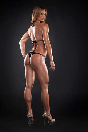 hand on hip: Sexy bodybuilder girl posing to camera. Full length back view isolated over black background Stock Photo