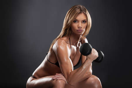 dumbbells: Beautiful sexy fit woman doing exercise for biceps. Lifting dumbbells isolated on black background