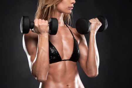 Close up of fit muscular woman lifting dumbbells. Cut out of bodybuilder isolated on black photo