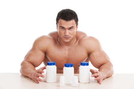 Muscular handsome bodybuilder with pills and dope. Sitting isolated over white background Stock Photo