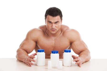 Muskulös schön Bodybuilder mit Pillen und dope. Sitzen isoliert über weißem Hintergrund Lizenzfreie Bilder