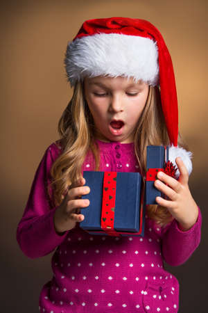 christmasy: Little blond girl looking surprise with new year present. Looking inside the gift box in Santa Claus hat