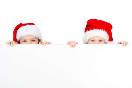 Two little kids looking over white poster in red Santa hats. Only eyes visible isolated on white background photo