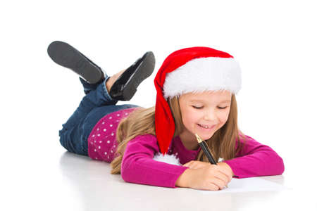 Beautiful little blond girl writing letter to Santa Claus. While laying isolated on white in Santa Claus hat photo