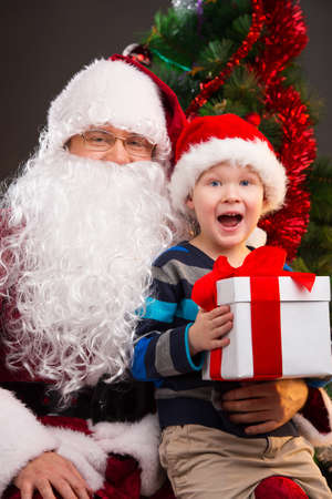 Little boy getting present from Santa Claus. Looking happy and surprised while sitting on Santa knees photo
