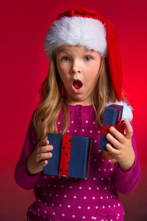 christmasy: Surprised little girl with open gift box. Standing over red background in Christmas hat