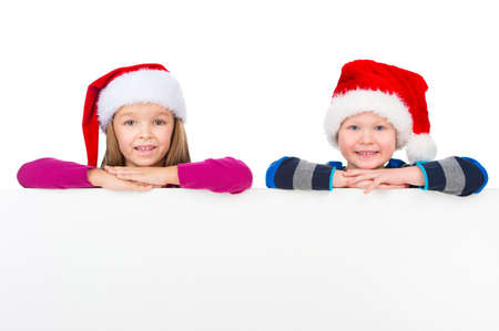 brother and sister: Two little kids in Santa Claus hats resting on white board. Smiling on camera over white poster isolated on white background
