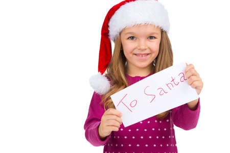 Little smiling girl holding letter for Santa Claus. Looking at camera and standing over white background photo