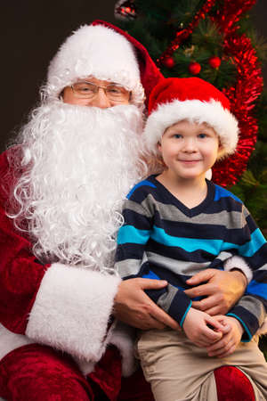 Little funny boy sitting on Santa Claus laps. Looking together on camera and smiling. photo