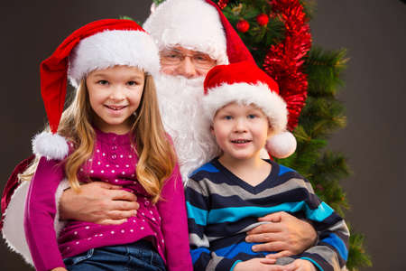 lap: Old kind Santa Claus holding two little kids on his knees. Smiling and looking at camera with Christmas tree on background