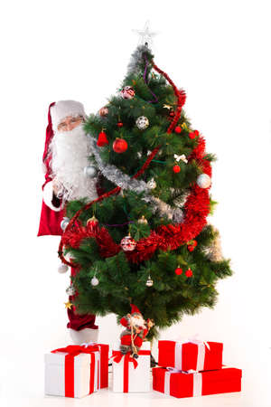 Big Christmas tree with a lot of presents under and Santa Clause behind. Old Santa Claus looking over tree isolated on white photo