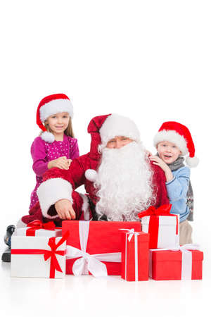 Old Santa Claus surrounded kids and presents. Sitting together isolated over white background photo