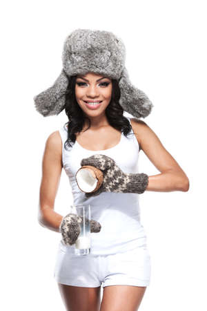 Beautiful smiling African woman pouring coconut milk. While standing in winter hat in gloves isolated over white background photo