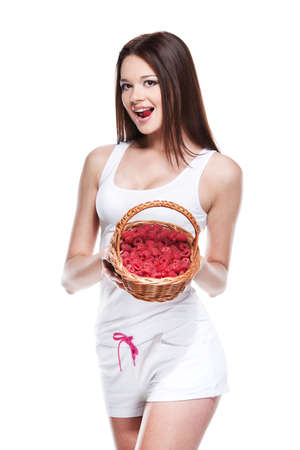 Sexy brunet girl in white clothes posing on camera. Holding fruit basket isolated over white background photo