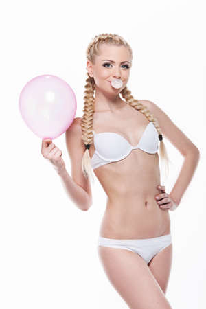 bubble gum: Beautiful blond girl posing with pink balloon and bubble gum. Standing in white lingerie isolated over white background