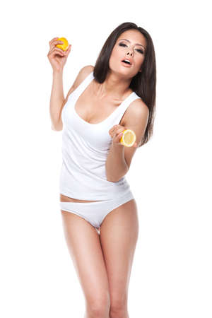 Sexy Asian brunet girl in white underwear. Holding two halves of lemon and standing isolated over white background photo