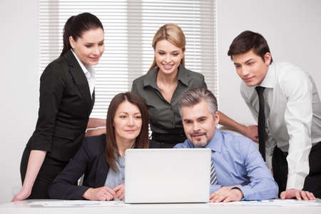 Large group of people looking together at laptop. Smiling and searching something, discussing ideas
