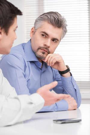 Porträt von schweren Geschäftsmann mittleren Alters. Sitzen und Hören von jungen Erwachsenen Kollegen
