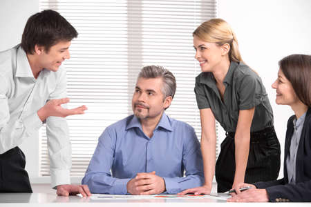 mixed age: Mixed age business team having brain storm meeting. Sitting at the table smiling in light modern office