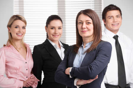 Successful adult business woman standing with crossed arms. Happy successful business team standing on background photo