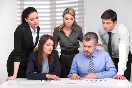 Zakelijke bijeenkomst van vijf mensen uit het bedrijfsleven verschillende leeftijd. Bespreking en planning in de moderne lichte kantoor