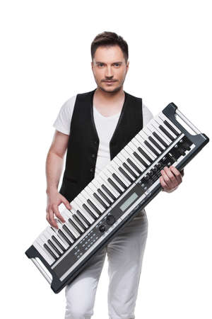 Sexy handsome man with synthesizer. Standing isolated over white background Stock Photo