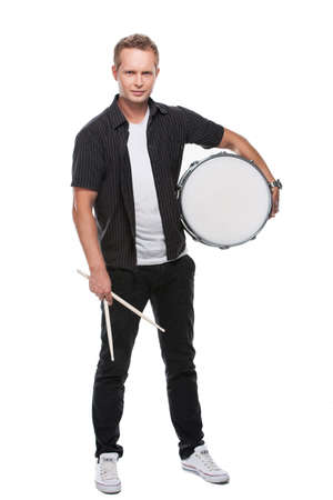 Sexy blond male drummer looking at camera. Holding white drum standing isolated over white background