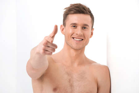 man pointing up: Close up of Sexy handsome man smiling on camera. Pointing with finger on camera while isolated over white  Stock Photo